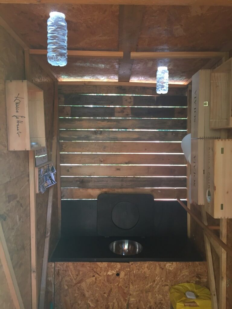 Outhouse that lights up in the dark with water and alge from bottles placed in the celing.