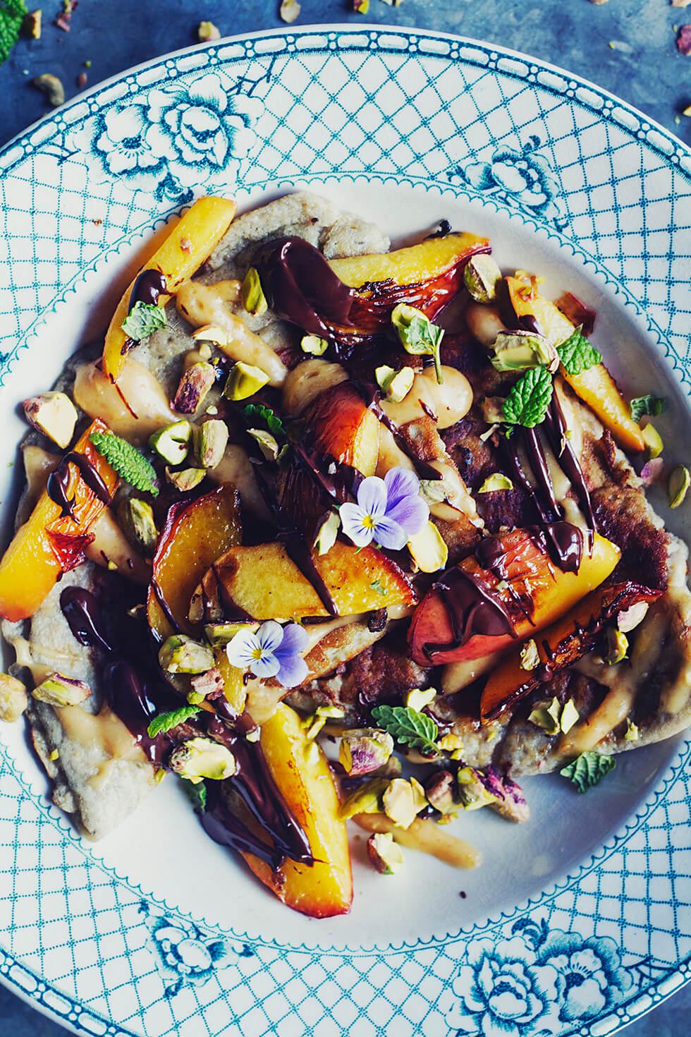Banapannkaka med stekt nektarin, jordnötssås, chokladsås och pistagenötter