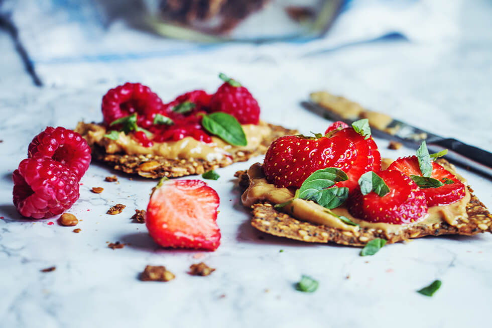Glutenfritt fröknäcke med jordnötssmör, hallon och jordgubbar på