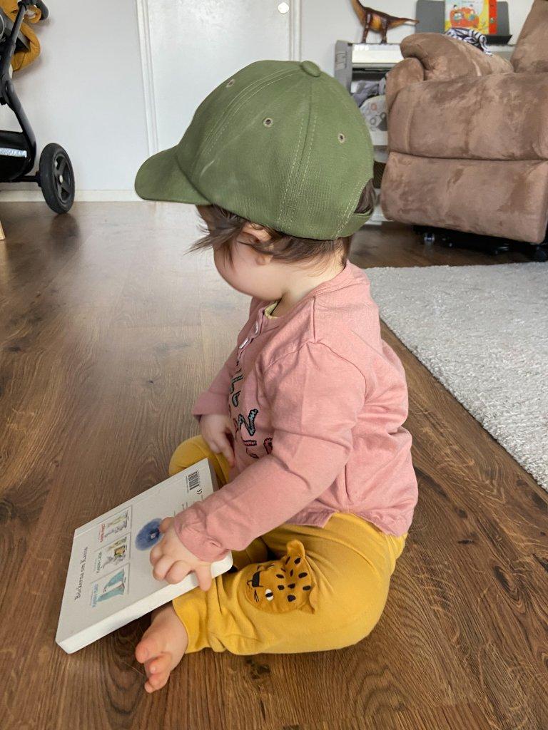 Bebis sitter med en bok