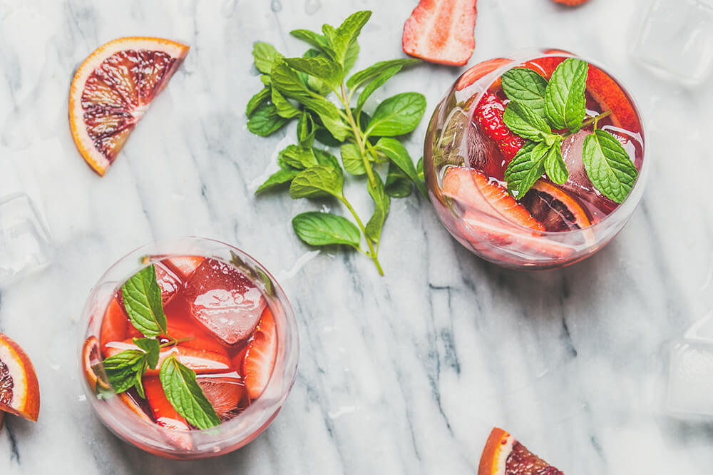 Blood orange and strawberry summer Sangria. Fruit refreshing rose wine cocktails in glasses with ice and mint over grey marble background, top view, square crop